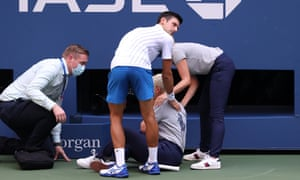 Novak Djokovic tends to a line judge after hitting them accidentally