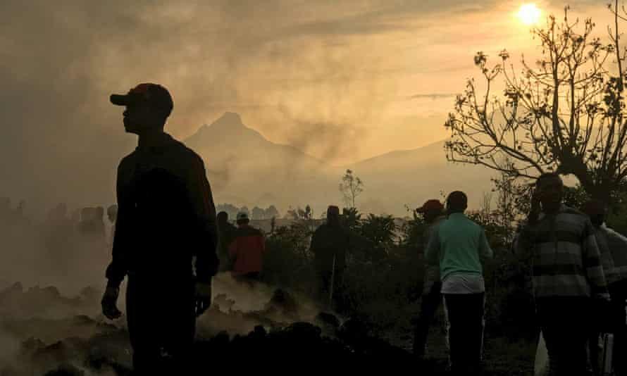Los residentes caminan cerca de las casas destruidas después de la erupción del monte Nyiragongo cerca de Gom