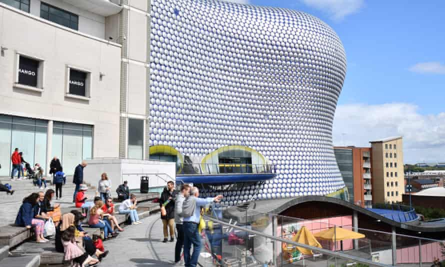 People sit outside the Bullring shopping centre in Birmingham.