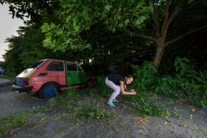 Slavica, Stanko's sister, pretends to be a jumping fox next to an abandoned car in Spandau.