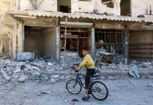 A boy sits on a bicycle in front of damaged shops in the al-Qaterji neighbourhood