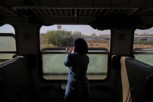 A woman looks out of a window from of a train travelling through the outskirts of the city.