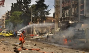 Syrian emergency personnel extinguish the smouldering facade of the Al-Dabbeet hospital after rocket attack.