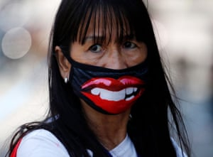 A woman wears a face mask featuring glossy red lips at a market in Manila, Philippines