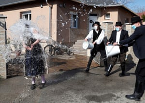 A woman is obscured by water thrown from buckets held by three men wearing black and white clothes.