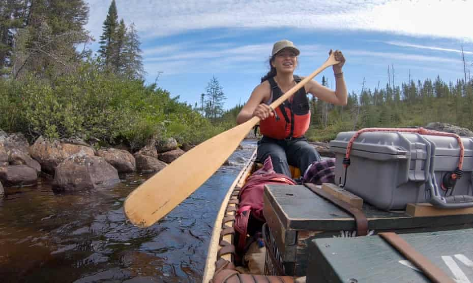 Woman paddling a canoe laden with stores down a river in the Canadian wilderness