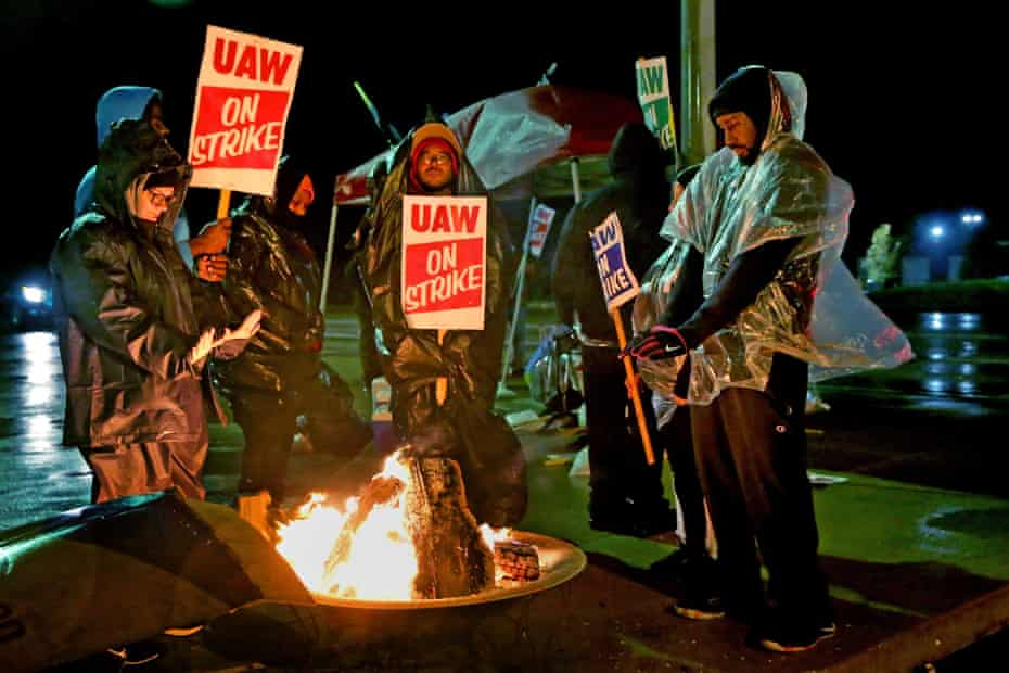 UAW workers stay form by the fire as they picket the GM plant in Wentzville, Montana. Economic anxiety and anger are also fueling the wave of strikes.