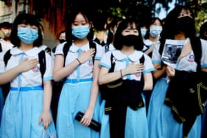 Hong Kong, China: schoolmates of student Tsang Chi-kin, who was shot in the chest by police during violent pro-democracy protests, place their hands on their chests during a demonstration at their school