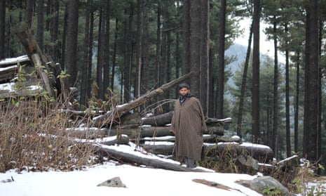 Abdul Aziz stands with the rubble of his forest hut in Khatana Ludro.