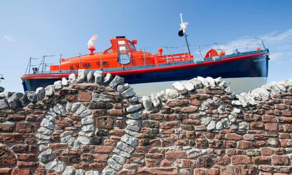 An old lifeboat and a stone wall made to look like waves outside the Dock Museum in Barrow in Furness