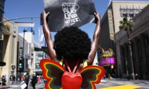 A protester strikes a pose while holding a Black Lives Matter sign on Hollywood Boulevard during the All Black Lives Matter solidarity march, replacing the annual gay pride celebration, on Sunday in Los Angeles.