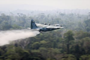 A C-130 Hercules aircraft dumps water to fight fires burning in the Amazon rainforest, in Brazil, Saturday, Aug, 24, 2019. B
