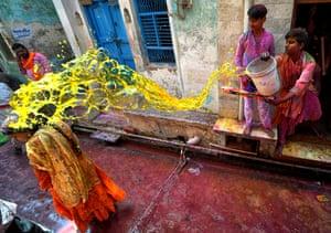Mathura, India. A man throws coloured water onto a woman during the Lathmar Holi Festival of Barsana