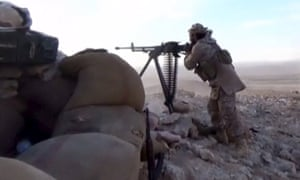 An Isis fighter fires a machine gun in this still image taken from a video said to be taken on the outskirts of Palmyra and uploaded on 21 March.