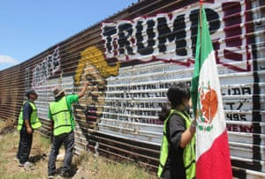 Mexican nationals deported from the US protest by graffitiing over an image of Donald Trump on a section of the border fence between Mexico and the United States.
