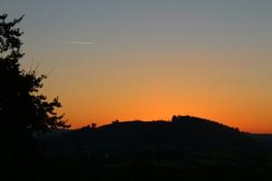 A cloudless dawn sky graduates towards red