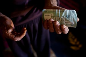Mohammad Raabah shows the Lebanese banknotes he will use to buy food in Zahlé