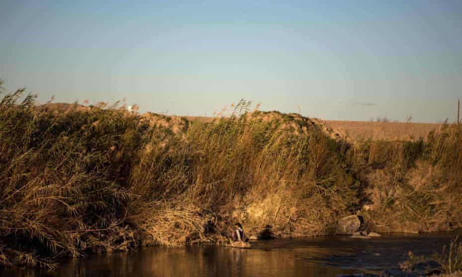 A woman crossing the Rio Bravo with a baby on the US/Mexico border in Ojinaga, in northern Mexico.