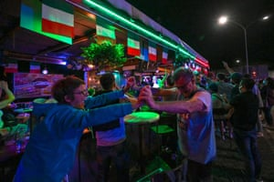 Fans of Italy react after Italy scored their third goal, as they watch in a bar in Rome.