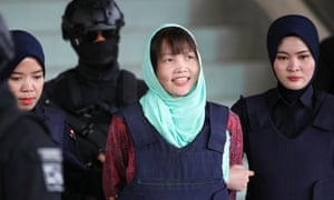 Doan Thi Huong (central) smiles as she is escorted by Malaysian police officers at the high court in Shah Alam, Malaysia.