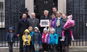 Lord Dubs, with community leaders, foster carers and children, hands in a petition to No 10 on 11 February