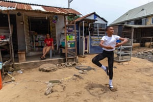 A student performs a dance routine in front of his mother's shop in Okelola street