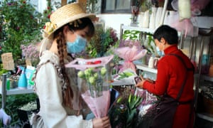 People shop in a flower market in Suzhou, one of the cities where the digital currency will be trialled.