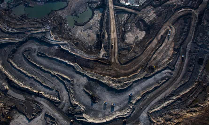 Trucks and machinery along routes within the Suncore oil Sands site near Fort McMurray in Northern Alberta, Canada