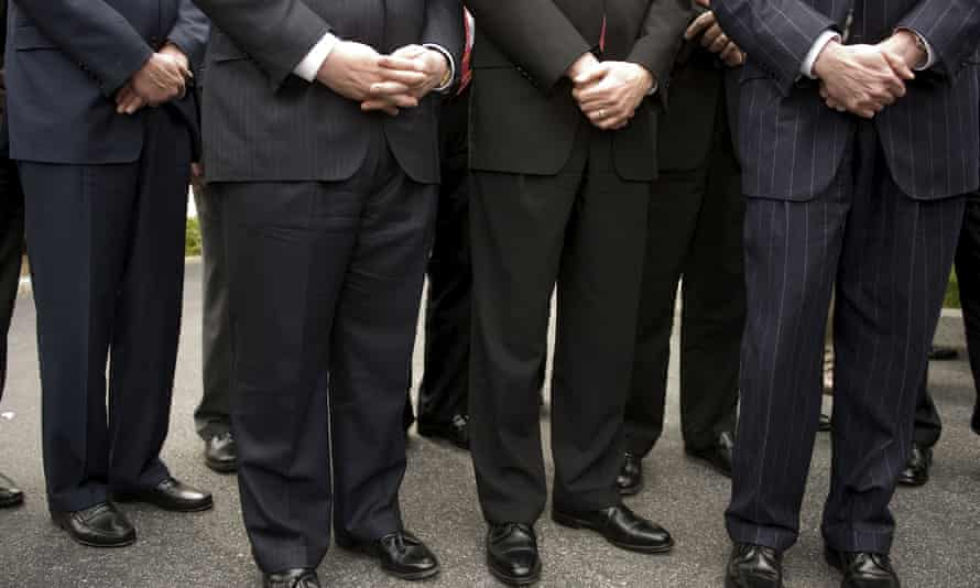 Legs and feet of financial CEOs standing in a line.