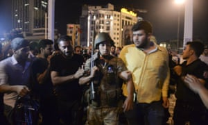 A Turkish soldier, arrested by civilians, is taken to be handed over to police officers