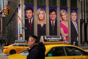 Traffic on Sixth Avenue passes by advertisements featuring Fox News personalities, including Bret Baier, Martha MacCallum, Tucker Carlson, Laura Ingraham, and Sean Hannity, adorn the front of the News Corporation building, March 13, 2019 in New York City.