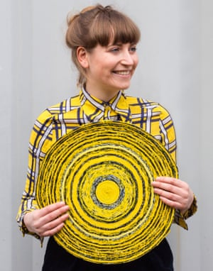 Simone Post with a round yellow rug made from trainers.