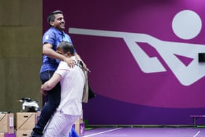 Iran's Javad Foroughi is lifted up by his coach Mohsen Nasr Esfahani after winning the men's 10-metre air pistol.