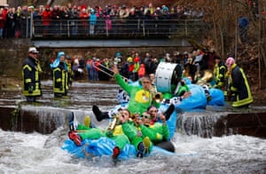 Schramberg, Germany: People on homemade rafts ride down the Schiltach stream in a race as part of the town's carnival celebrations