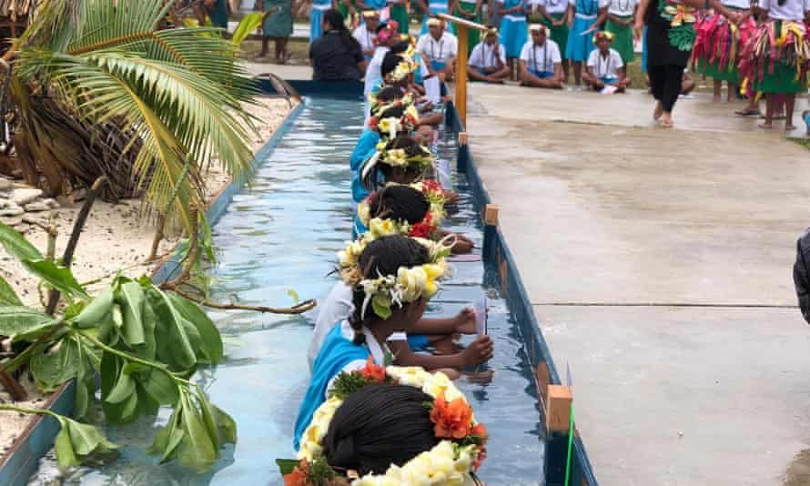 Children from Tuvalu sit in a moat of water