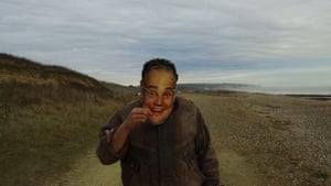 Project Art Works: The Mask, 2017. Project Art Works is a collective of visual artists. They work towards greater neurodiversity and representation in culture and care. In The Mask, Sharif Persaud walks along the coast from Hastings to the De La Warr Pavilion in Bexhill, wearing a mask of comedian Al Murray as the Pub Landlord. Persaud's improvised dialogue is delivered to camera in both his real voice and that of his mask persona. The film celebrates his own idiosyncratic behaviour whilst including moments of candid revelation about his experience as a young man with autism.