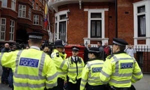 Police officers stand outside the Ecuadorian embassy in London
