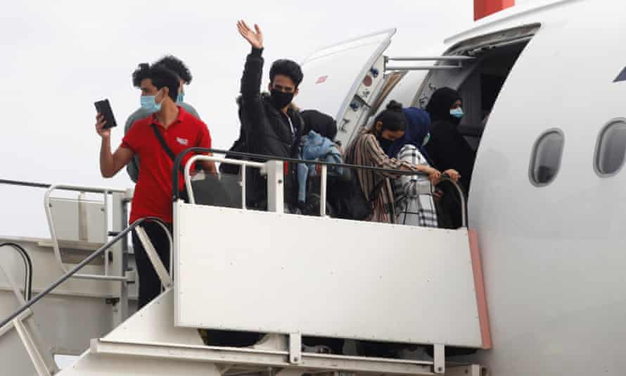 Refugees from overcrowded migrant camps board their flight to the UK at Athens international airport.