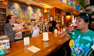 Bar staff and a female customer, sipping a beer, at Vine Street Brewery, Denver, Colorado, US.