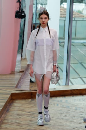 A classic white shirt is elevated into a dress with netting trim and see-through sleeves.