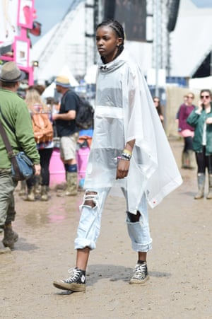 Model Leomie Anderson braves the 2016 mud in a weather-friendly poncho and perhaps less weather-friendly ripped jeans and Converse.