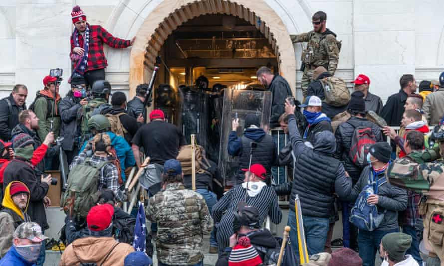 Rioters clash with police trying to prevent them from entering the Capitol's front doors in Washington DC on 6 January.