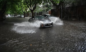Wet weather: a car drives through flood water in Melbourne