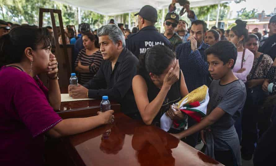 Family members and fellow officers mourn pay tribute to the officers killed in an ambush on Monday. At least 30 gunmen opened fire on the convoy of state police officers.