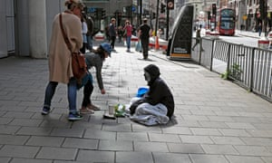 Girl putting money into the cup of poor homeless man