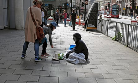 A girl putting money coins into the cup of a homeless man begging on the street in London.
