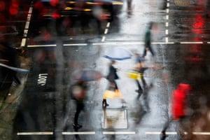 People cross a wet road in Sydney