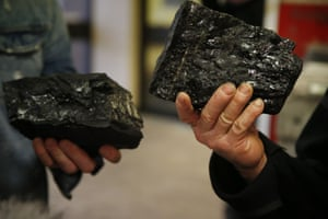 Two coalminers hold up souvenirs of their last day of work.