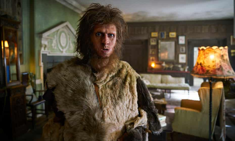 Still from the TV series Ghosts, showing Robin the Caveman in a living room