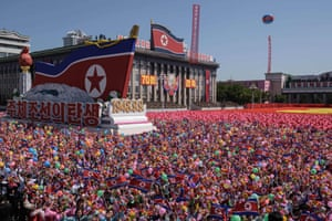 Participants wave flowers in North Korea's 70th anniversary parade